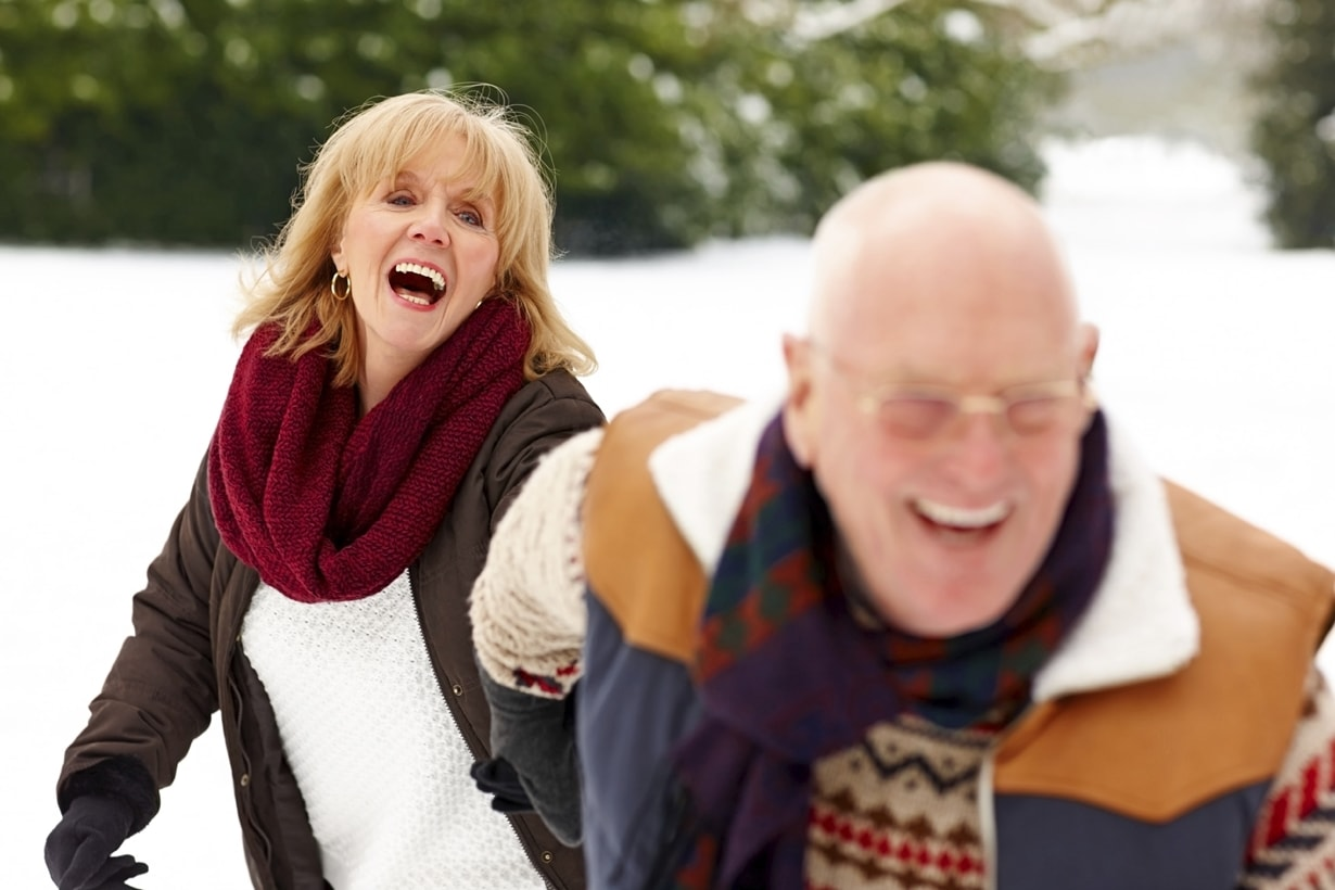 A more senior couple holding hands and laughing in the snow