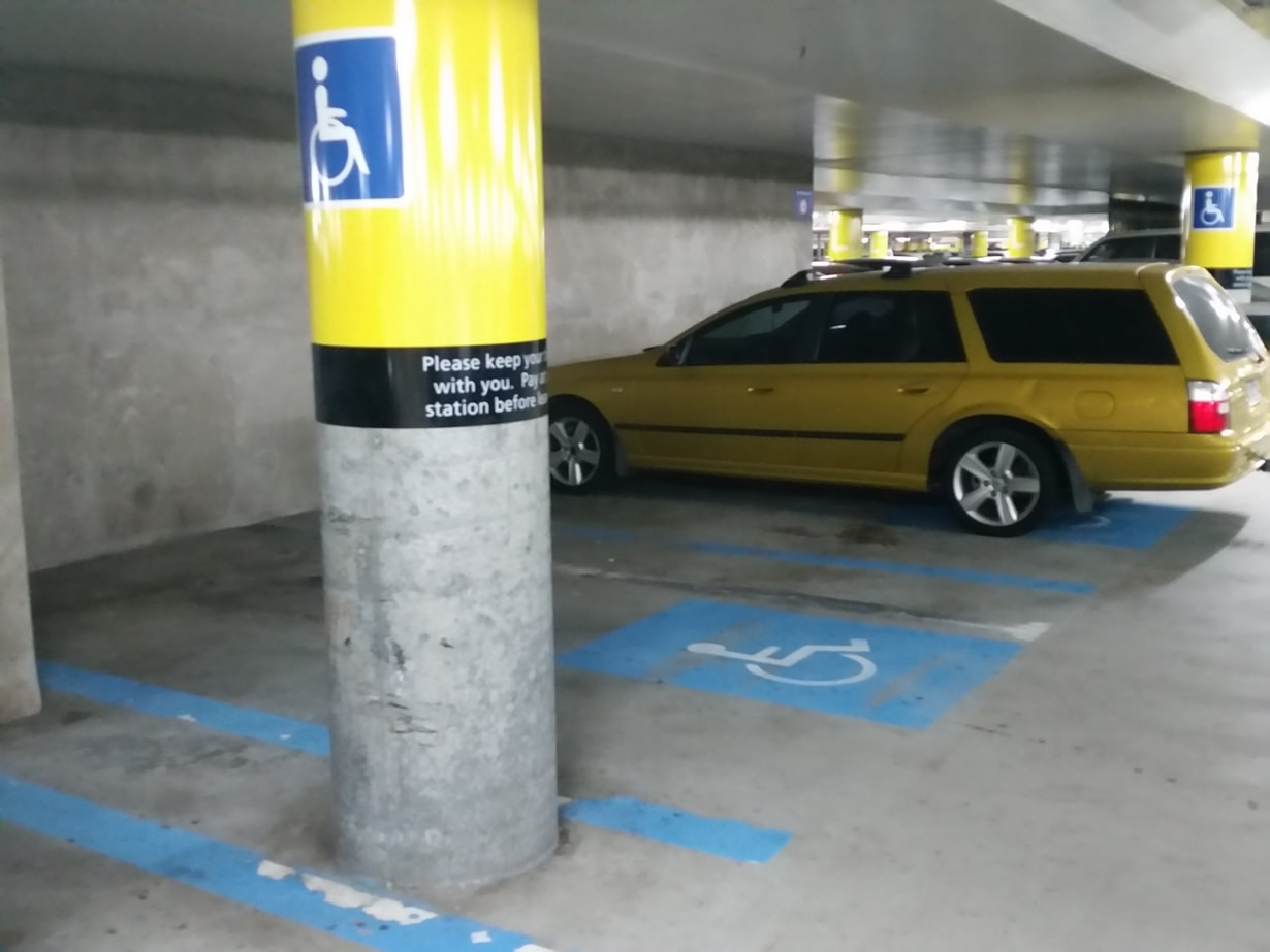 Accessible car parking space in basement level, with a large yellow sign with blue wheelchair symbol on a column