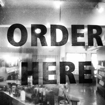 black and white restaurant with ORDER HERE sign on window